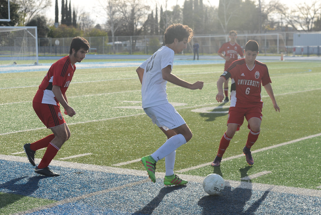 . Pleasant Valley High\'s Tomas Oliveras (23) tries to keep the ball from University High\'s Kian Chamine (8) and Nico Perry-Mitchell (6), Thursday, March 8, 2018, in Chico, California. (Carin Dorghalli -- Enterprise-Record)