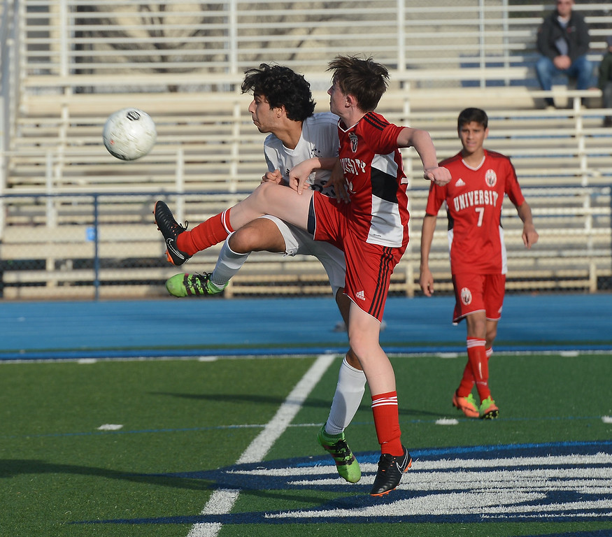 . University High\'s Owen Flanagan (12) and Pleasant Valley High\'s Tomas Oliveras (23) try to kick the ball at the same time, Thursday, March 8, 2018, in Chico, California. (Carin Dorghalli -- Enterprise-Record)