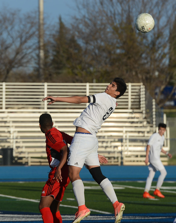. Pleasant Valley High\'s Jasiel Celis (22) head butts the ball as he\'s defended by University High\'s Chase Lane (13), Thursday, March 8, 2018, in Chico, California. (Carin Dorghalli -- Enterprise-Record)