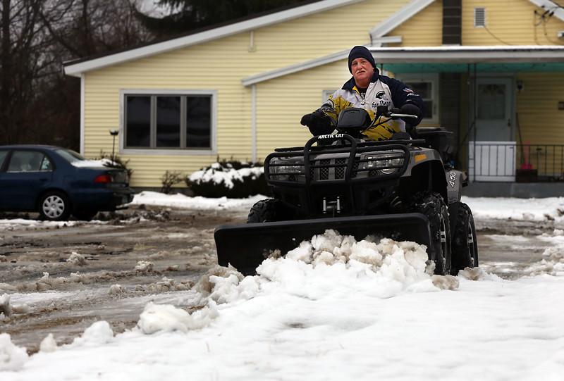 HOLLY PELCZYNSKI - BENNINGTON BANNER Wayne Powers. of Bennington Vermont plows out his driveway, filled with heavy slushy snow, on Monday morning.