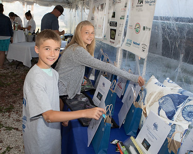 Alli and Sean Powderly drop raffle tickets in to prize bags at the Bass & Blue Captains and Crew Kickoff Dinner Event. Wicked Local Photo/Denise Maccaferri