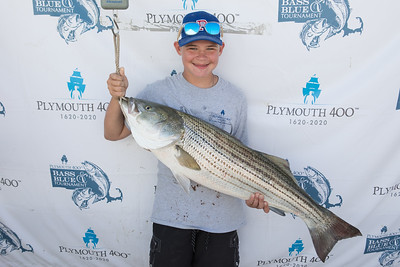 Johnathan Nero, 14, proudly shows off the striped bass he caught to earned him 3rd Place in the Youth Category.   Wicked Local Photo/Denise Maccaferri