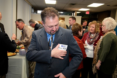 Plymouth Area Chamber of Commerce Executive Director Denis Hanks puts on a name tag for the last time at Thursday's monthly Business After Hours event.