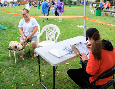 Stella Berrardi, of Pembroke, and her dog Billie, named after Bill Belichick, pose for caricaturist, Shawn Eetrin from Worcester.