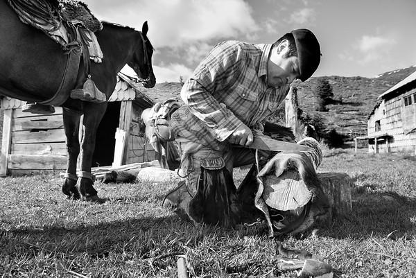 Oscar cortando un cuero de vaca para hacer un lazo. Los pobladores gauchos fabrican sus propias herramientas