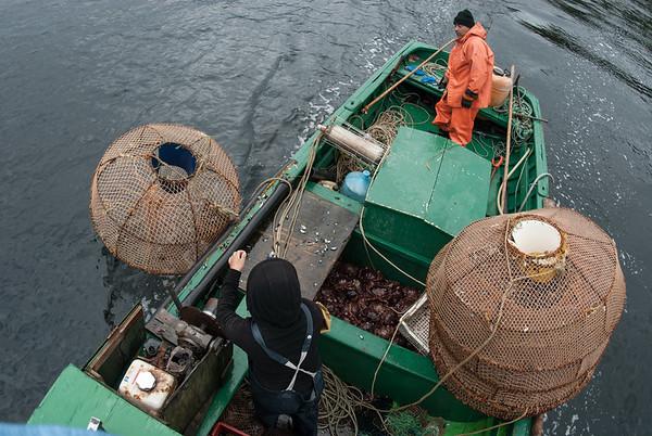 Móise y su hija Chabe lanzando las trampas de jaiba al mar