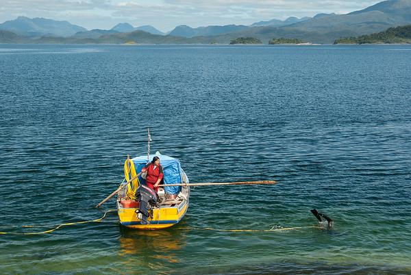 Blanca y Juan se apoyan en el trabajo del mar. Blanca maneja la lancha mientras Juan bucea mariscos
