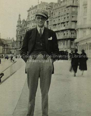 Giorgio Joyce standing in street wearing cap, hands in pockets
