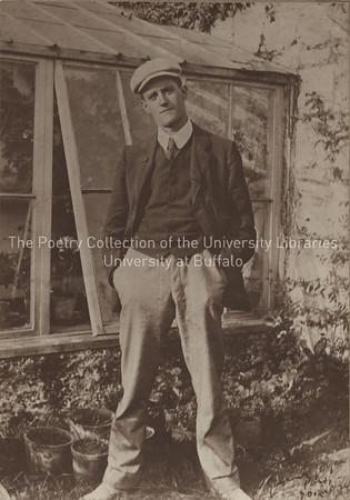 James Joyce standing beside greenhouse, Dublin