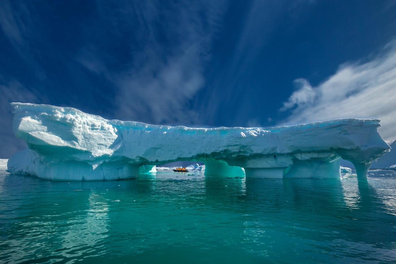 zodiac behind iceberg in Antarctica