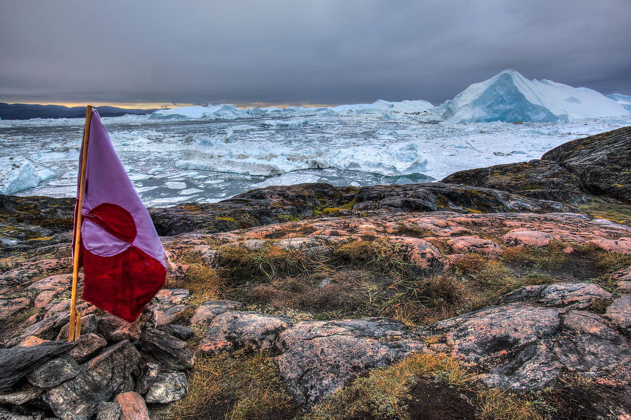 The Greenlandic Flag sits motionless on a Glacial Background