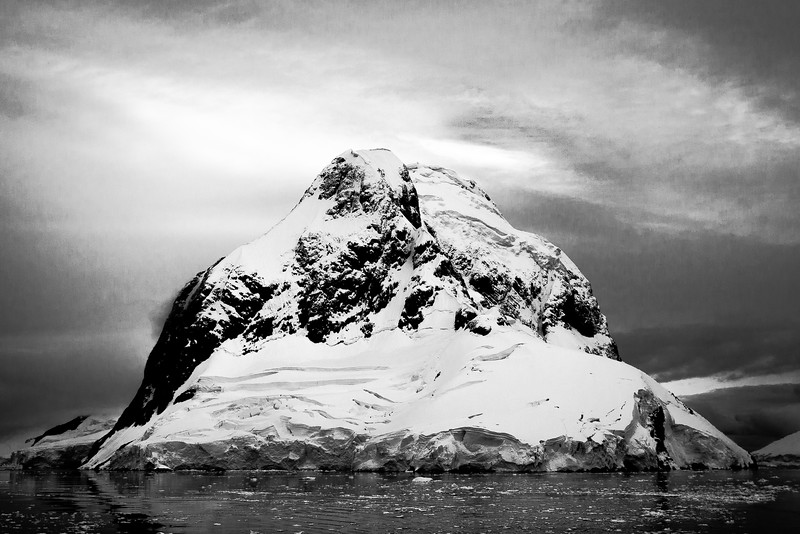 An abrupt rock peak rises into the snowy skies in the Lemaire Channel, Antarctica