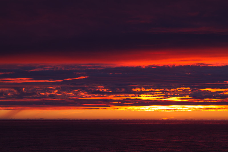 A spectacular Arctic sunset illuminates the cloud layers above.