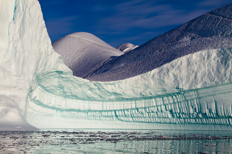 An ice pipe organ unfolds as you turn the corner into this magnificently sculpted ice bay, repetitive pipes below, dappled fields above, in RØdefjord, Greenland