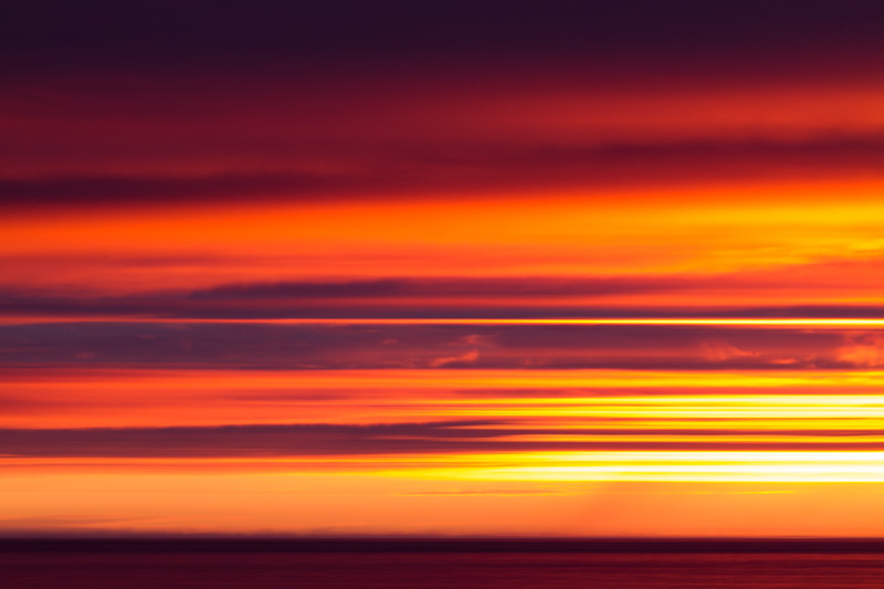 An Arctic sunset made abstract, blurring parts of the cloud layer and sea by panning the camera on a tripod with a slow exposure (0.6s)