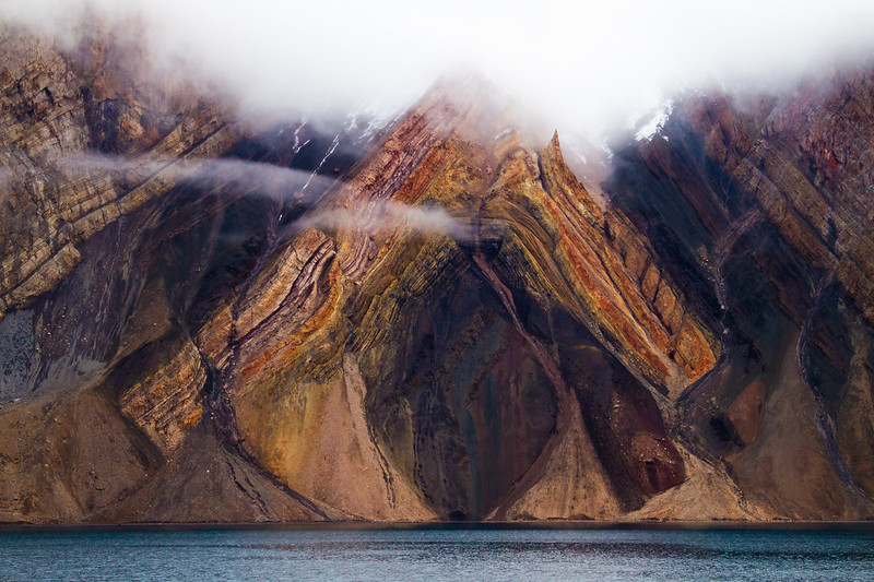 A massive rock fold shows the power of the earth's geologic processes erupting from the steep, jagged slopes of King Oscard Fjord in Greenland, highlighted in the vivid reds and orange of this V shaped formation.Processing: minor crop, saturation and curves