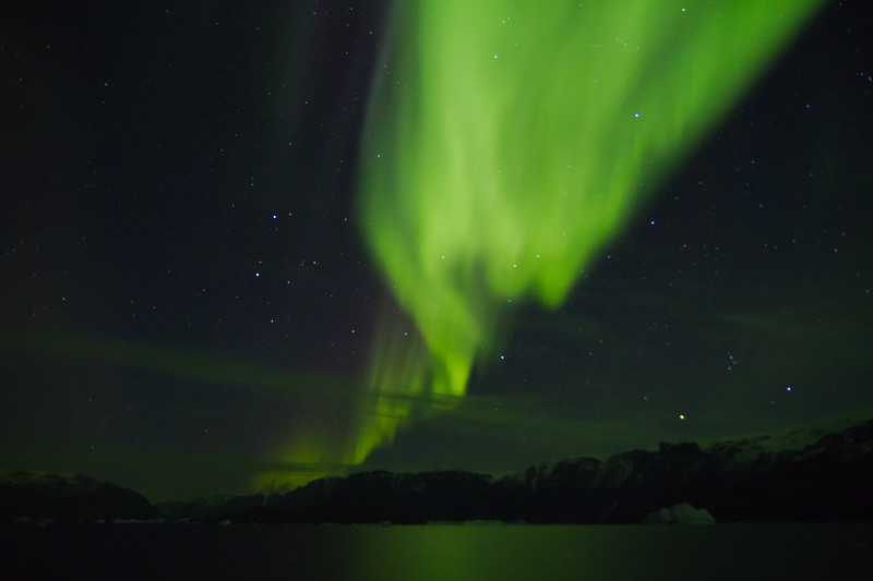 Curtains of green aurora borealis twist over the icebergs and mountains of Rypefjord, Greenland