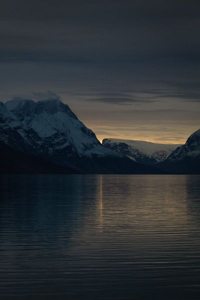 The final moments of sunset diffract up and through the narrow conjunction of two Arctic mountains, reflecting as a thin line across King Oscar Fjord, and peace descends over the landscape.