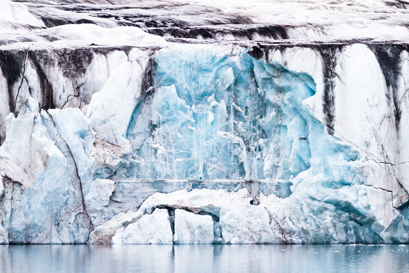 A gothic ice formation resembles a waterfall both above and in the descent, in St Jonsfjorden, Svalbard.