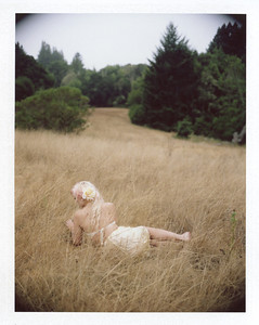 An instant film boudoir photo, inspired by Andrew Wyeth, of a woman in lingerie in a field facing away from the camera