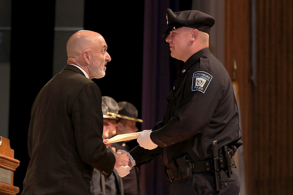 . Cadet Ryan Richard gets his certificate from Municipal Police Training Committee (MPTC) Executive Director Daniel Zivkovich during the Fitchburg State University\'s 1st recruit officer course graduation on Thursday September 13, 2018. SENTINEL & ENTERPRISE/JOHN LOVE