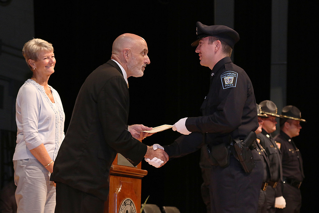 . Cadet John Francis gets his certificate from Municipal Police Training Committee (MPTC) Executive Director Daniel Zivkovich during the Fitchburg State University\'s 1st recruit officer course graduation on Thursday September 13, 2018. SENTINEL & ENTERPRISE/JOHN LOVE
