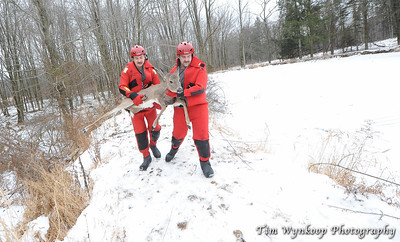 Harmony Township firefighters, John Latourette, left and Kyle McKenna, carry the doe away from the pond.