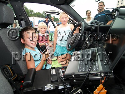 Washington Township (Warren County), NJ, 08-07-2007: Caroline Cotte, 8, is in the driver's seat of a Washington Township police car during the township's National Night Out celebration Tuesday. Looking on are Cassie Romanczuk, 5, left and her sister, Brittany Romanczuk, all of Washington Township. (Photo by: Tim Wynkoop)