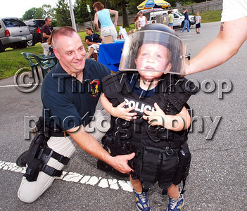 Phillipsburg, NJ, 8/5/2008, (Tim Wynkoop Photo): Phillipsburg Police Officer William Vine helps support three-year-old Ryan Baylor, after he put on heavy armourment vest at the towns National Night Out ceremony Tuesday at Phillipsburg Police Headquarters.