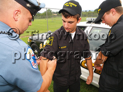 Alpha, NJ, 8/5/2008, (Tim Wynkoop Photo): Pohatcong Township Patrolman, Anthony Goodell, helps Pohatcong Township Police Explorer, Nicholas Acevedo, center, and Sam Ansman, both of Pohatcong Township, gear up for National Night Out at Alpha Borough Park Tuesday.