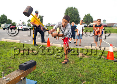 Greenwich Township, NJ, 8/5/2008 (Tim Wynkoop Photo): Alex Lopez, 11, of Greenwich Township, swings a rubber hammer to ring the bell at the Greenwich Township National Night Out Tuesday.