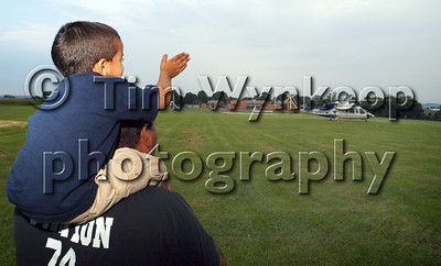 Lopatcong Township, NJ, 8/5/2008, (Tim Wynkoop Photo): Jonathan Abraham, 3, of Lopatcong Township, sits on his dad's (Shibu) shoulders as he wave goodbye to a New Jersey State Police Helicopter at the Lopatcong Township National Night Out ceremony Tuesday at the township's firehouse on Strykers Road.