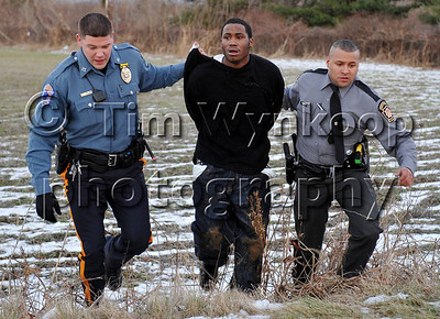 Pohatcong Township, NJ, 12/25/2008:  Pohatcong Township Police Office, Ryan Barsony, left, and an unidentified Pennsylvania State Police Trooper take a man into custody in Pohatcong Township Thursday. The man is one of two men suspected in fleeing from a vehicle that crashed at Exit 3 on Route 78 West bound following a chase from Pennsylvania. Express-Times Photo | TIM WYNKOOP
