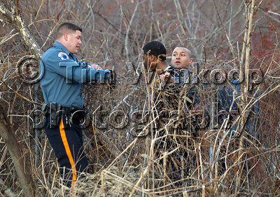 Pohatcong Township, NJ, 12/25/2008:  Pohatcong Township Police Office, Ryan Barsony, left, waits to assist an unidentified Pennsylvania State Police Trooper in removing a man from a wooded area along Route 78 East bound in Pohatcong Township Thursday. The man is one of two men suspected in fleeing from a vehicle that crashed at Exit 3 on Route 78 West bound following a chase from Pennsylvania. Express-Times Photo | TIM WYNKOOP