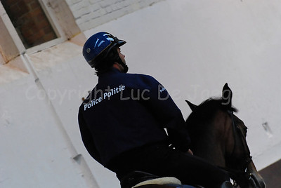 A member of the mounted police training the horse.