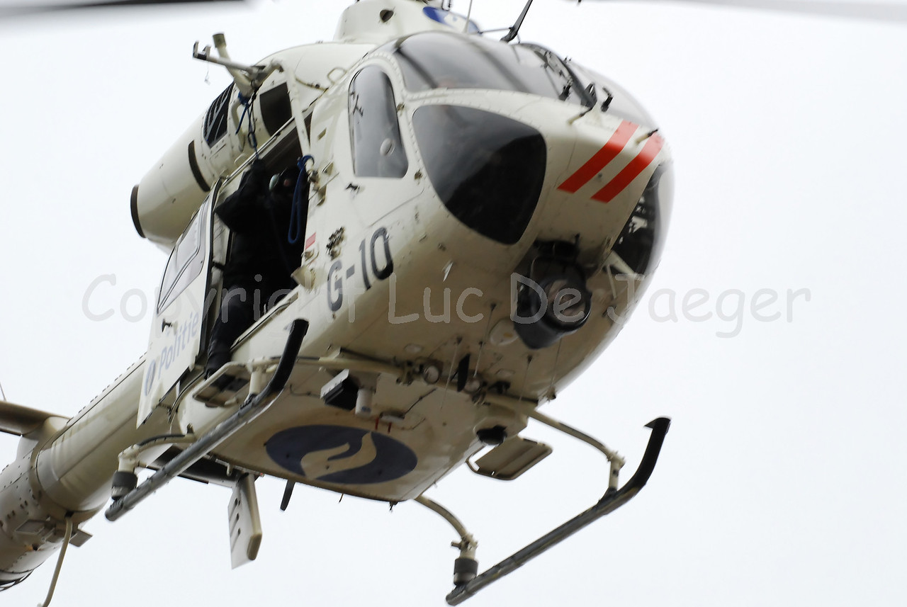 The McDonnell Douglas Explorer 900 helicopter of the Belgian  federal police with the so-called NOTAR system (No Tail Rotor). The MD 900 Explorer can fly at night and is equipped with other hi-tech material and gear. A member of the Special Intervention Squadron (SIE) hangs out. Photo captured during totally overcast weather.