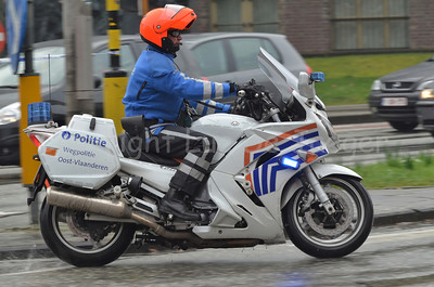 A motorcycle cop of the federal police of Belgium, riding on his Yamaha motorbike in the rain.