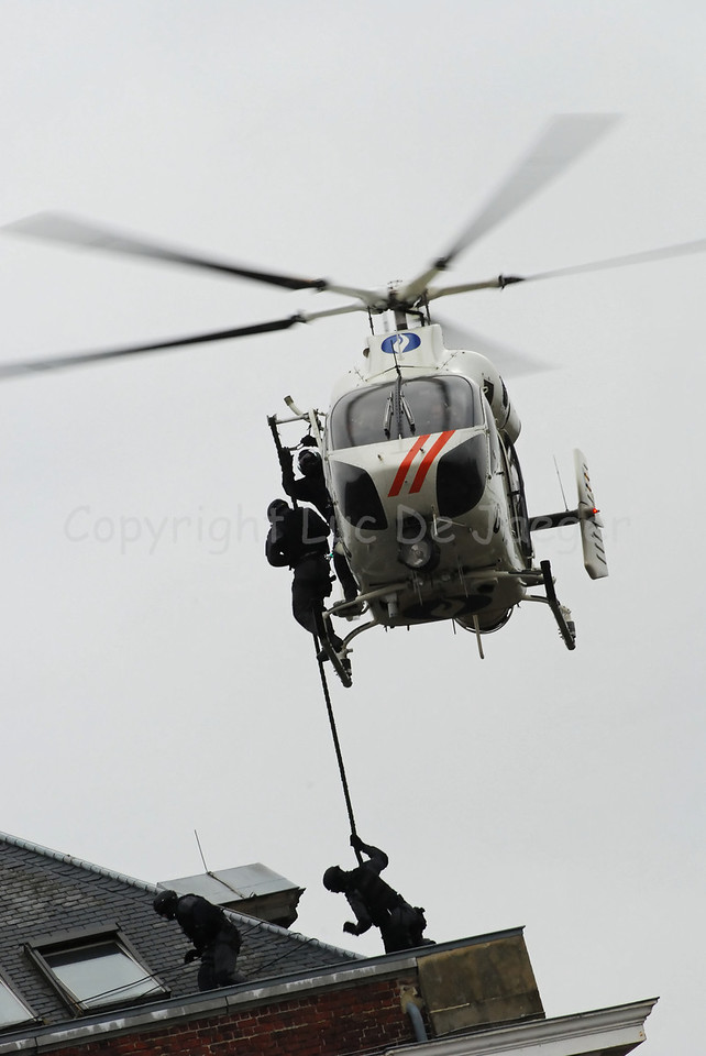 The McDonnell Douglas Explorer 900 helicopter of the Belgian  federal police with the so-called NOTAR system (No Tail Rotor). The MD 900 Explorer can fly at night and is equipped with other hi-tech material and gear. Members of the Special Intervention Squadron (SIE) descend rapidly down a rope. Photo captured during totally overcast weather.