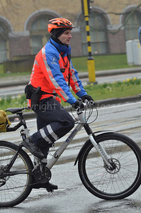 A bicycle cop of the local police of Ghent (Gent), Belgium, riding on his Cannondale mountainbike in the rain.