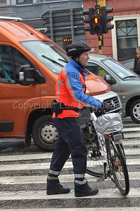 A bicycle cop of the local police of Ghent (Gent), Belgium, holding his Cannondale mountainbike in front of traffic lights for pedestrians.