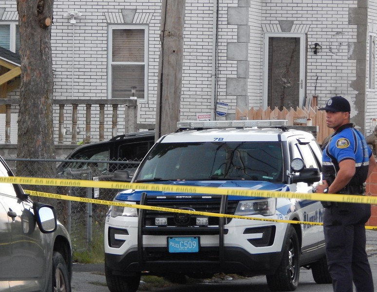 Police gathered outside a home on Queen Street in Lowell on Monday. Police and the District Attorney confirmed a death investigation is ongoing. AARON CURTIS/LOWELL SUN