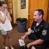 Lenaia Nolasco, 8, gets shy while greeting Officer Jeffrey Hurley and presenting him with handmade thank you cards at  Elm Street Community Church on Wednesday afternoon. SENTINEL & ENTERPRISE / Ashley Green