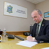 Fitchburg Police Chief Robert DeMoura signs some paper work at his desk in his office at the station. SENTINEL & ENTERPRISE/JOHN LOVE