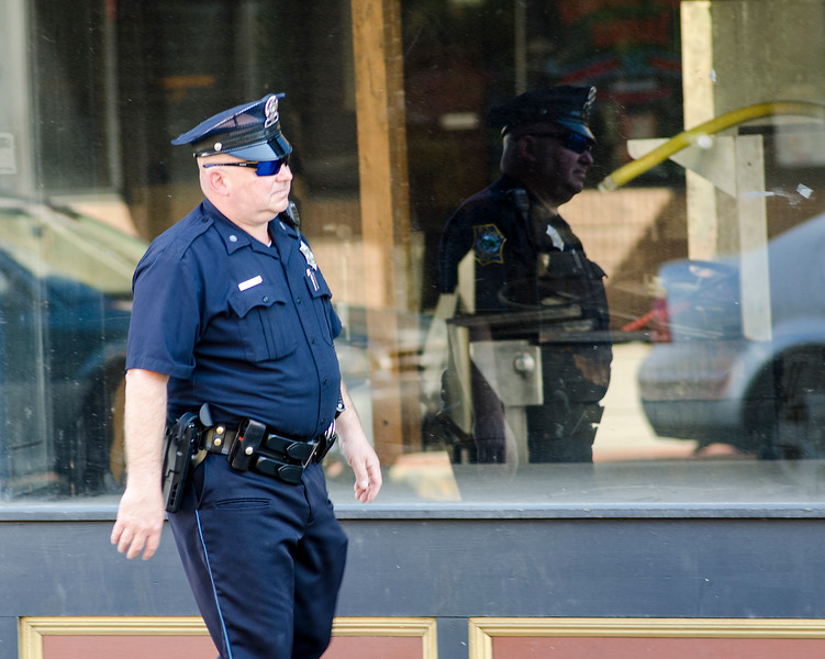 The Fitchburg Police Department has increased patrols on Main Street. Patrol Officer Rodney Conrad walks along lower Main Street on Wednesday afternoon. SENTINEL & ENTERPRISE / Ashley Green