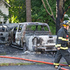 A Gardner Firefighter walks past the reamins of 2 cars that were set alight in the driveway of 99 Graham St.   SENTINEL&ENTERPRISE/ Jim Marabello