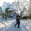 A Gardner police officer walks back towards his criuser after firefighters extinguished 2 cars on fire in the driveway at 99 Graham St. SENTINEL& ENTERPRISE/ Jim Marabello
