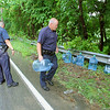Fitchburg police officers moved some five gallon water jugs off to the side of Ashburnham Road on Tuesday afternoon after a truck lost them and did not know it. The water was from Primo Purified Water. SENTINEL & ENTERPRISE/JOHN LOVE