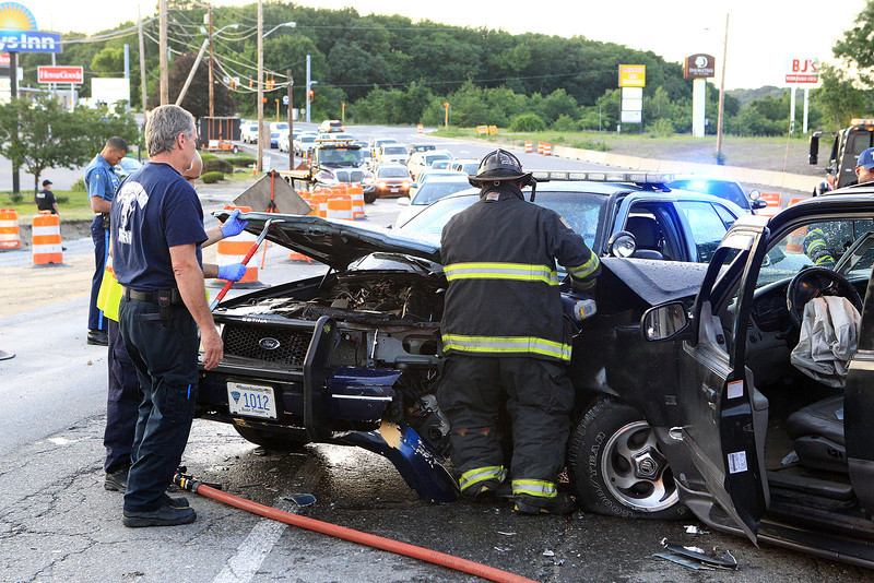Leominster Firefighter Robert Penning uses the jaws of life to open up the hood of the cruiser