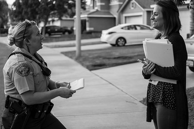 A deputy speaks with a child welfare case worker after accompanying her to check on the welfare of a child.