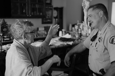 A deputy, conducting a welfare check, speaks with a elderly homeowner.